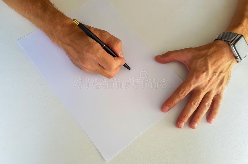 Zakenman die bij zijn bureau schrijven stock foto's