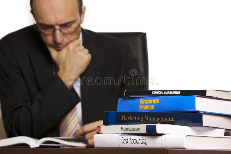 Zakenman die boeken bestudeert stock foto
