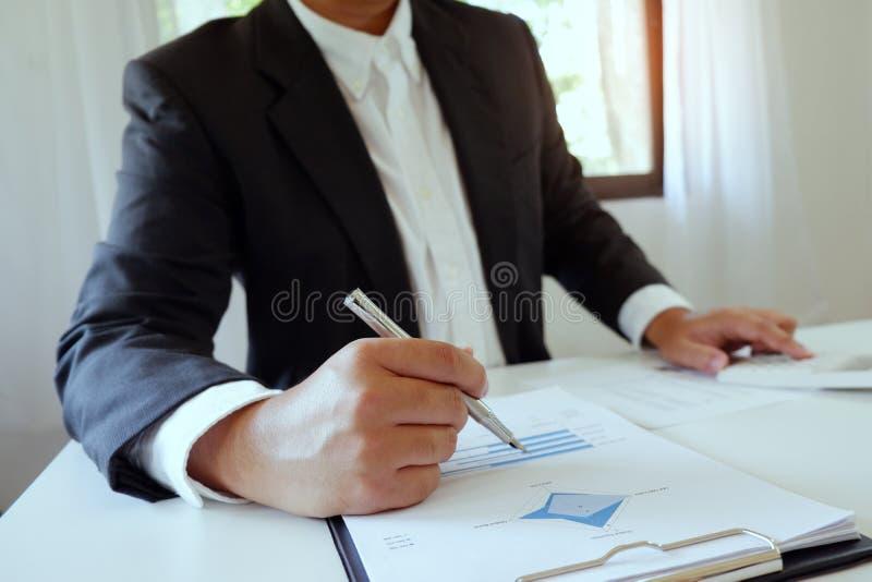 Zakenman die in bureau die calculator met document gebruiken aan bureau werken stock afbeeldingen