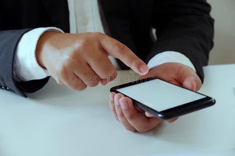 Zakenman die in bureau die mobiele telefoon met behulp van aan het bureau werken royalty-vrije stock foto's
