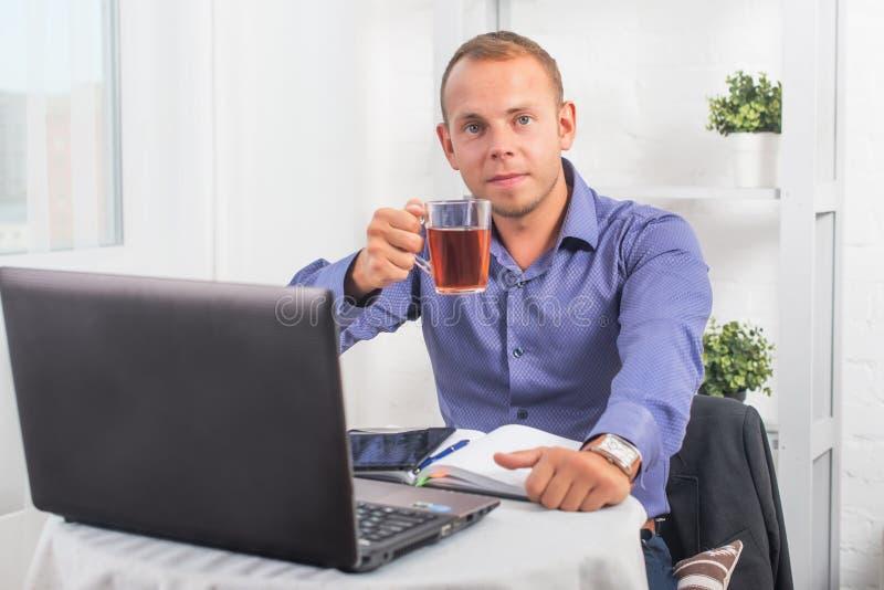Zakenman die in bureau werken, zittend bij een kop houden en lijst die recht kijken royalty-vrije stock foto
