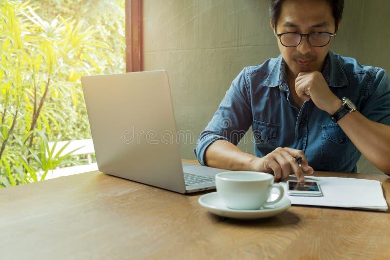 Zakenman die celtelefoon met laptop en koffiekop op houten bureau met behulp van royalty-vrije stock foto