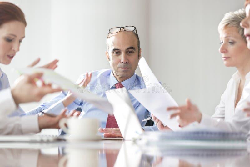 Zakenman die collega's bekijken die over documenten tijdens vergadering in bestuurskamer bespreken royalty-vrije stock afbeelding