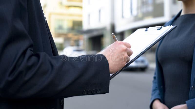 Zakenman die contract ondertekenen in openlucht, vrouwelijke medewerker die op document wachten stock afbeeldingen