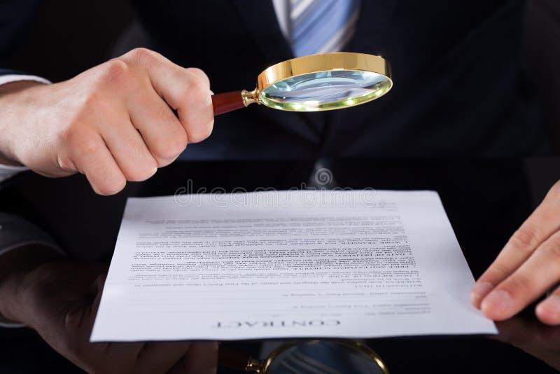 Zakenman die contractdocument met vergrootglas onderzoeken stock afbeeldingen