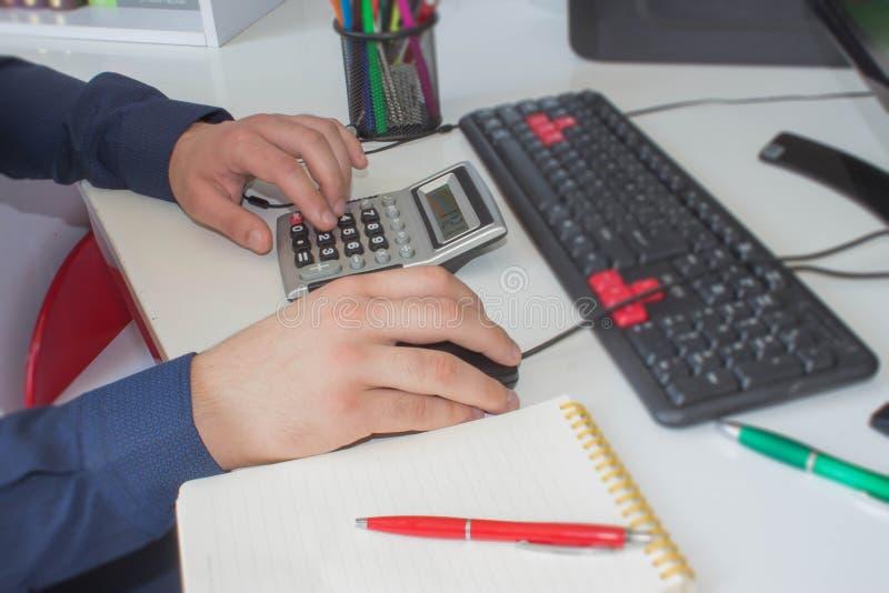 Zakenman die de financiële staten berekenen Sluit omhoog de jonge mens die met calculator die nota's thuis maken tellen royalty-vrije stock fotografie