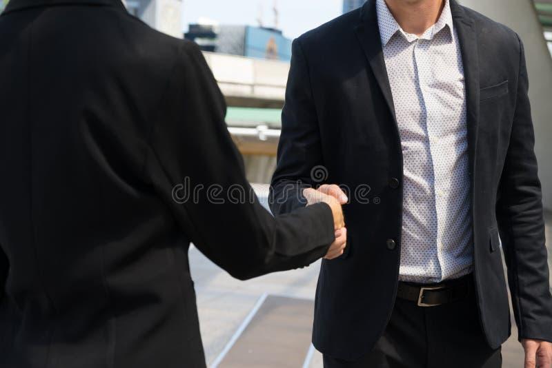 Zakenman die de handen schudde van zakenvrouw omdat hij aantoonde dat hij akkoord gaat met het ondertekenen van een contract tusse stock afbeelding