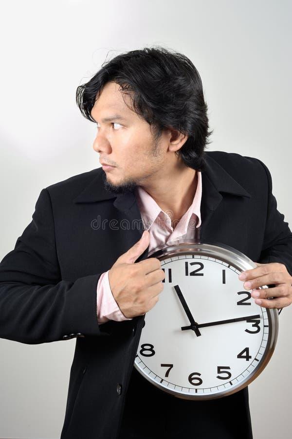 Zakenman die de klok stelen stock foto