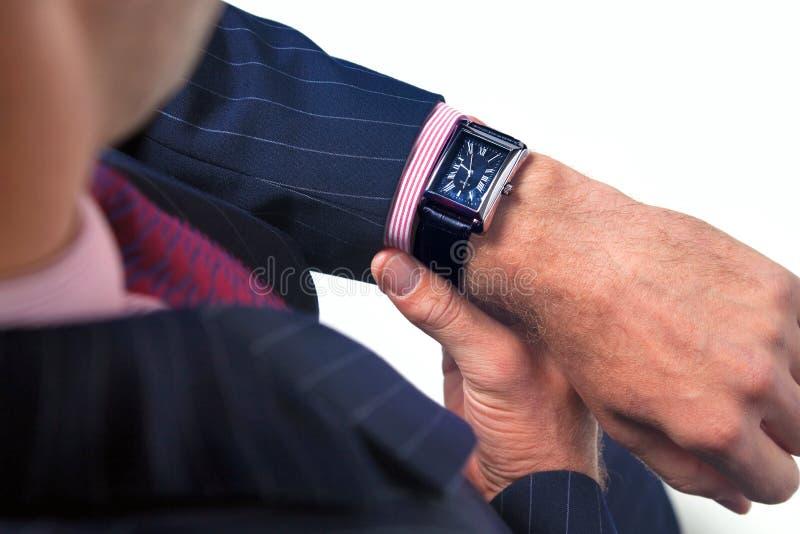 Zakenman die de tijd controleert op zijn horloge stock foto