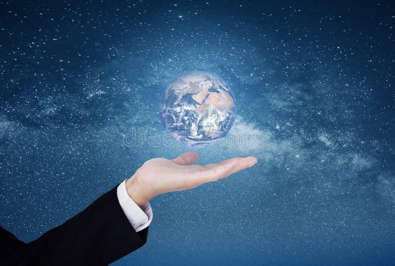 Zakenman die de wereld op hand, op blauwe sterrige ruimteachtergrond tonen Het element van dit beeld wordt geleverd door NASA stock foto's