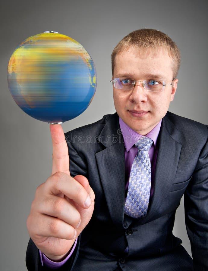 Zakenman die de wereldbol op vinger spint royalty-vrije stock foto