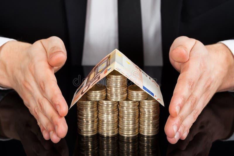 Zakenman die die huis beschermen van munt bij bureau wordt gemaakt stock afbeeldingen