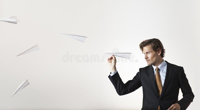 Zakenman die document vliegtuigen werpen bij doel stock afbeelding