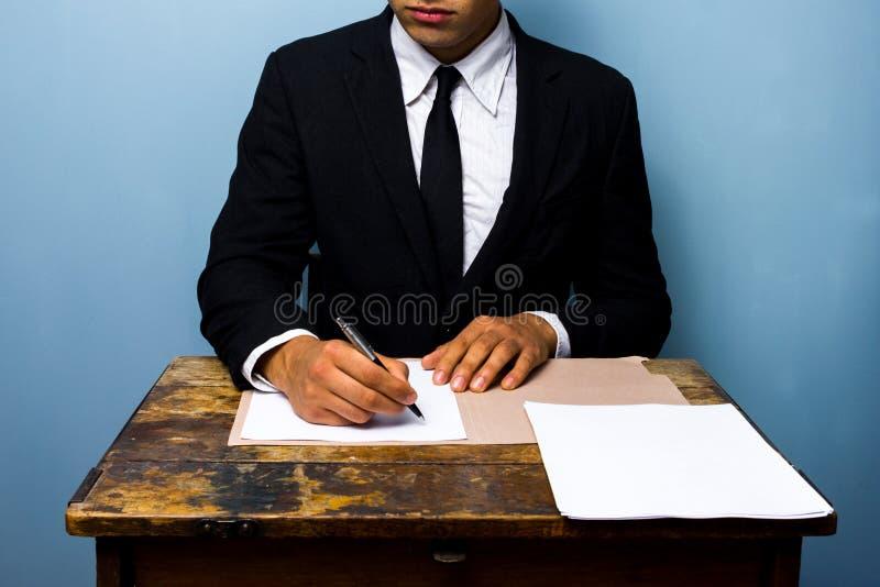 Zakenman die documenten ondertekenen bij houten bureau stock fotografie