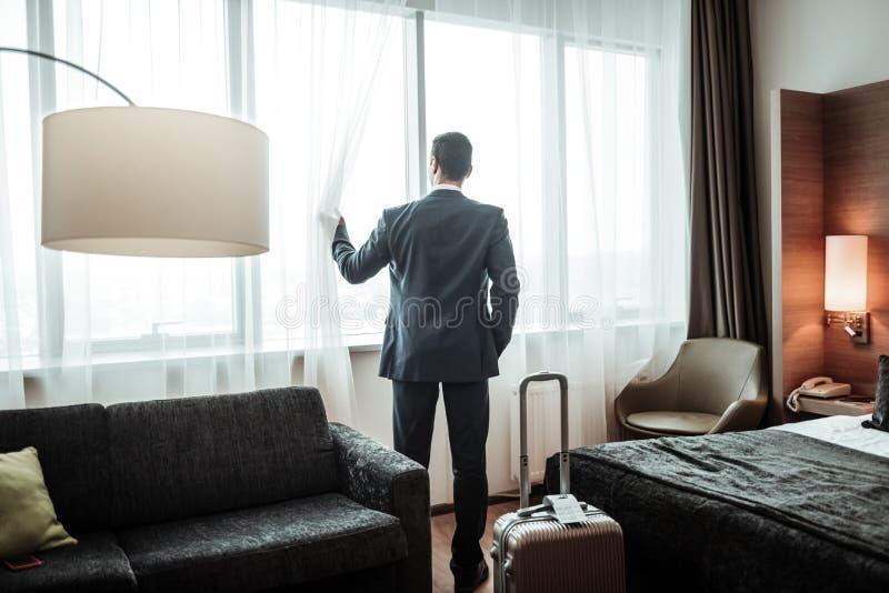 Zakenman die donker kostuum dragen die venster onderzoeken bij zijn hotel royalty-vrije stock afbeelding