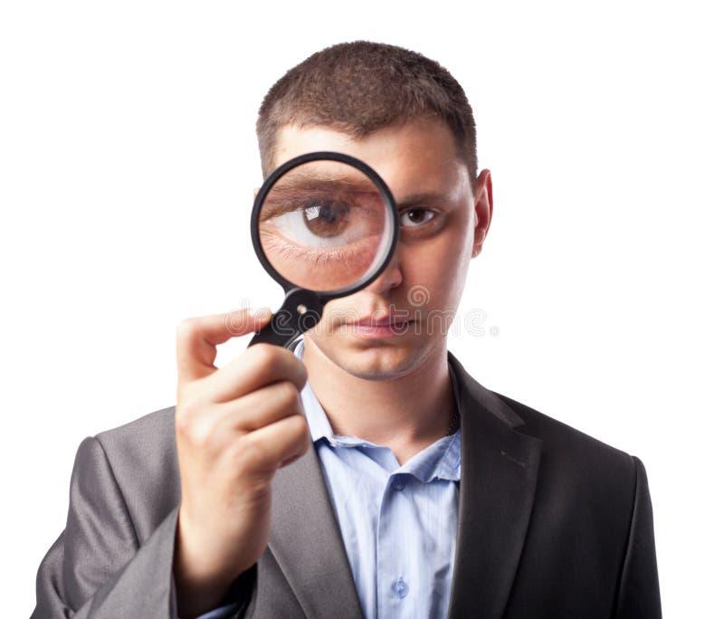 Zakenman die door een vergrootglas kijkt stock foto