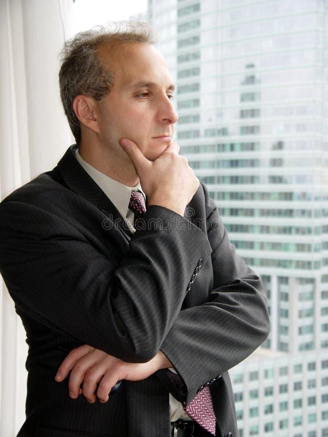 Zakenman die door het venster denkt stock afbeeldingen