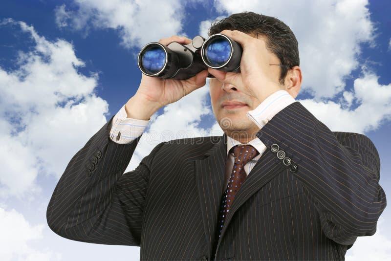 Zakenman die door verrekijkers kijkt stock foto