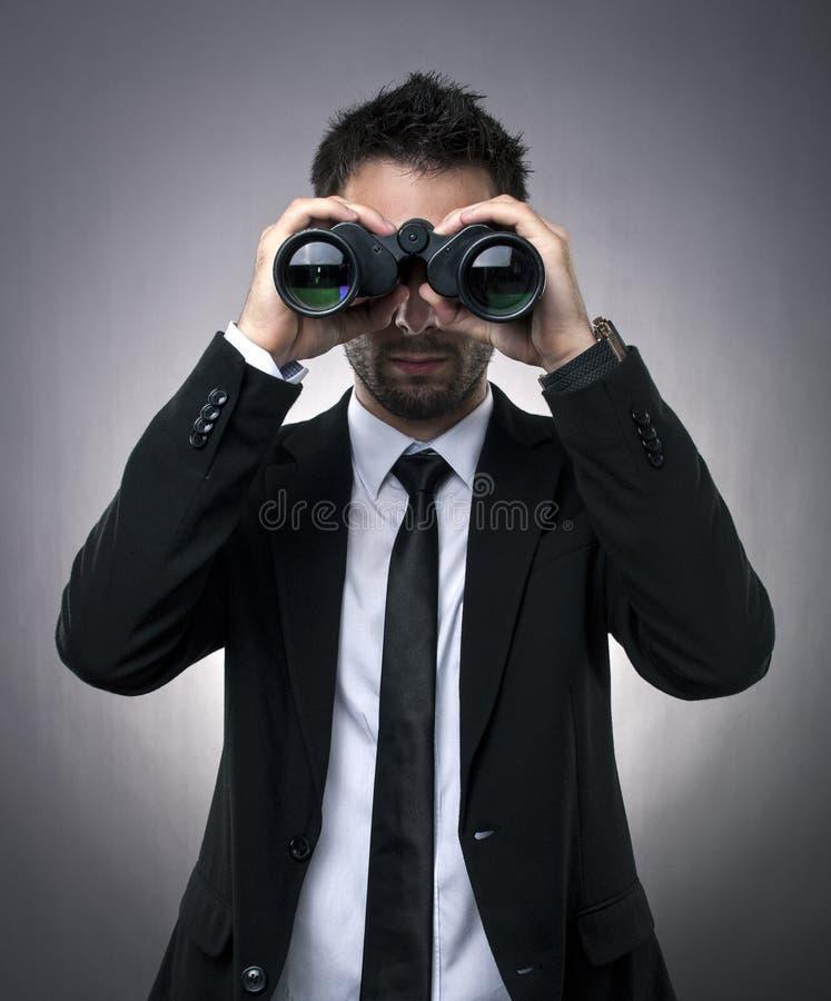 Zakenman die door verrekijkers kijkt stock foto's