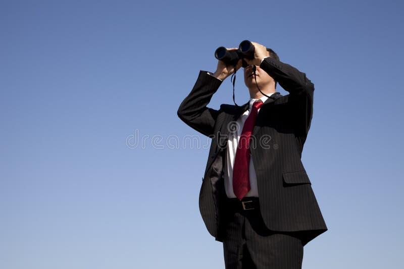 Zakenman die door verrekijkers kijkt stock afbeeldingen