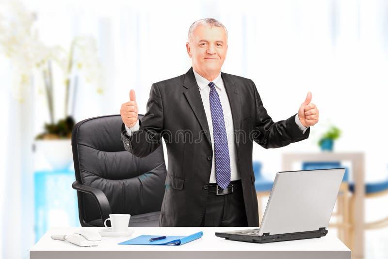 Zakenman die duimen in zijn bureau opgeeft royalty-vrije stock foto's