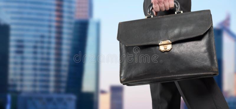 Zakenman die een aktentas met bureaugebouwen houden op achtergrond royalty-vrije stock afbeeldingen