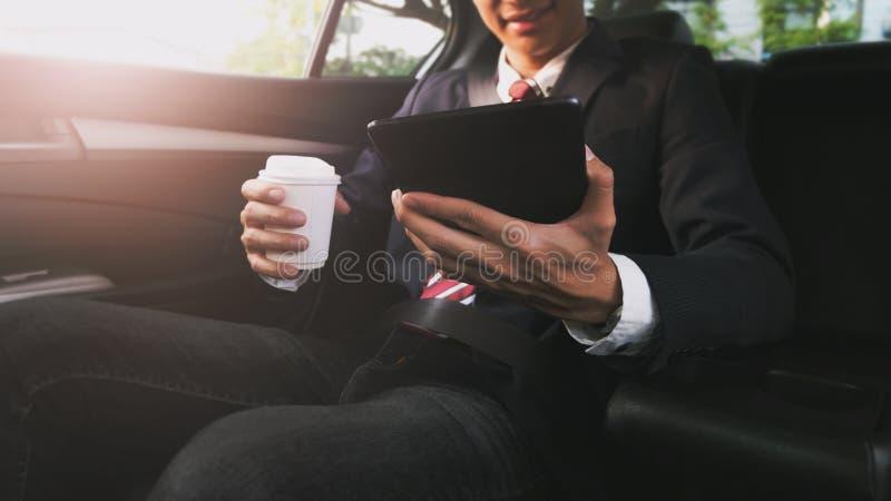 Zakenman die in een auto werken en een tablet gebruiken terwijl het drinken van koffie stock afbeelding
