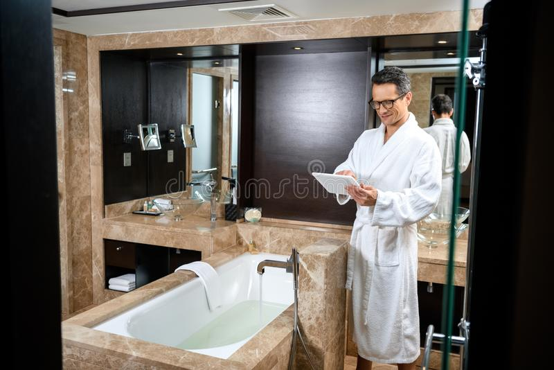 Zakenman die een badjas in hotelbadkamers dragen, die zijn digitale tablet gebruiken terwijl status stock foto's