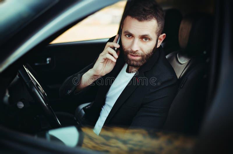 Zakenman die een cellphone in zijn auto gebruiken stock foto's