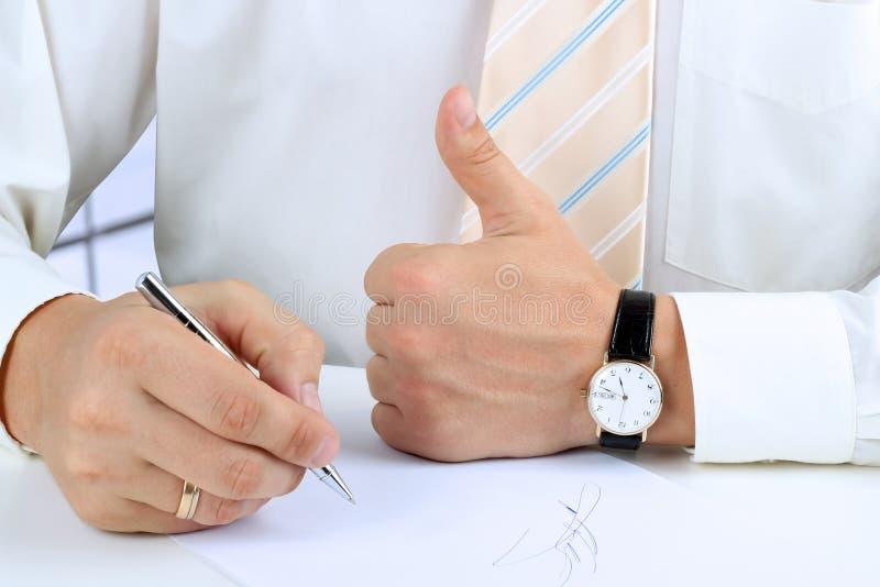 Zakenman die een document ondertekenen en O.K. teken met zijn thu tonen stock afbeeldingen