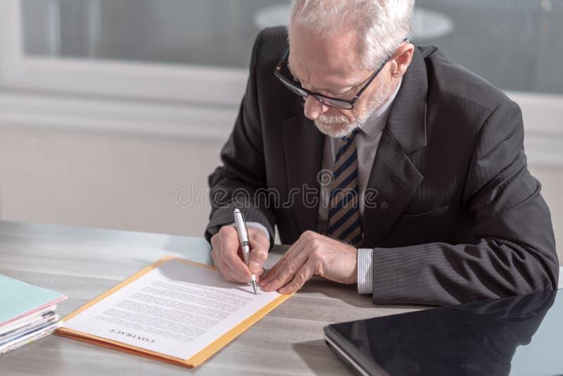 Zakenman die een document ondertekenen (gebruikte Lorem ipsumtekst) royalty-vrije stock fotografie