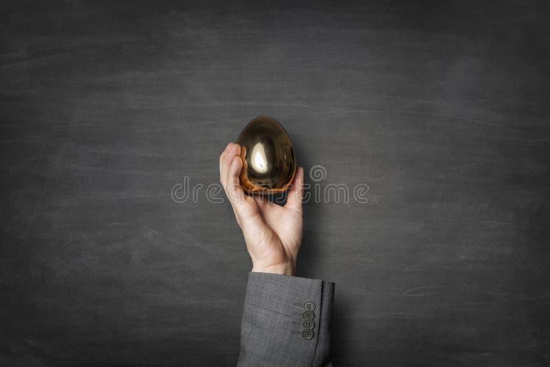 Zakenman die een gouden ei in een hand houden stock afbeeldingen