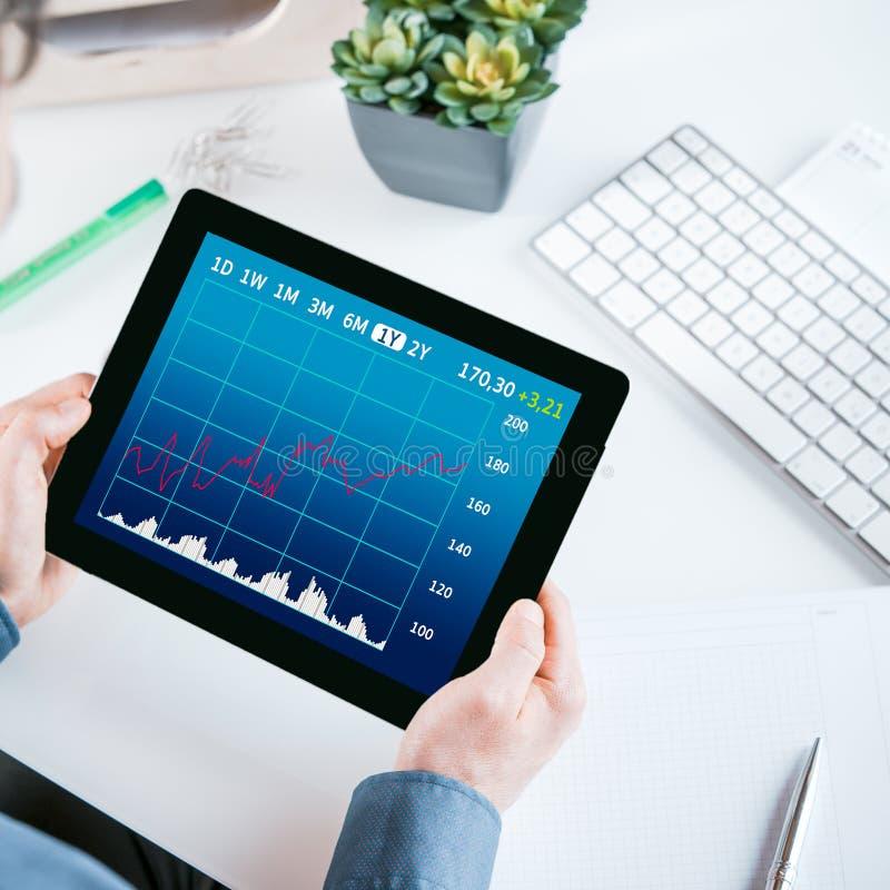 Zakenman die een grafiek op zijn tablet bekijken stock fotografie