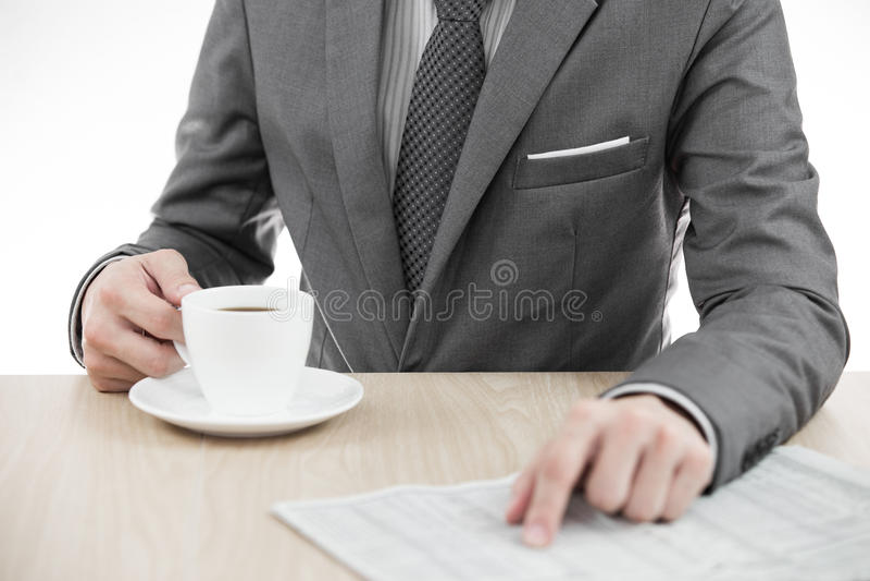 Zakenman die een kop van koffie houdt en een krant leest royalty-vrije stock foto