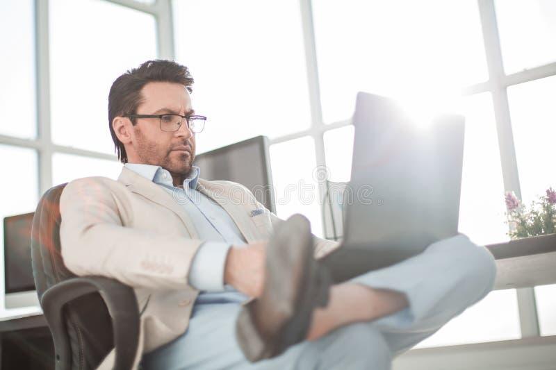 Zakenman die een laptop zitting gebruiken bij zijn Bureau stock foto