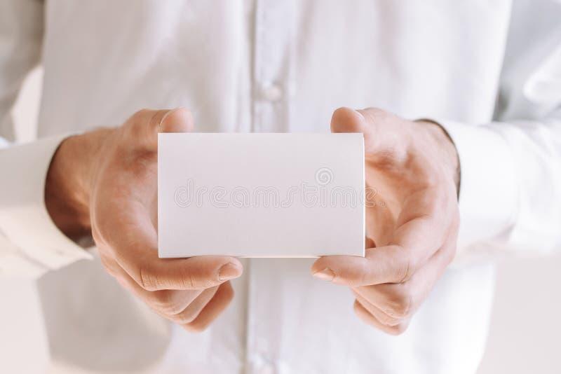 Zakenman die een leeg stuk van document tonen Zakenman in wit overhemd die adreskaartje geven stock fotografie