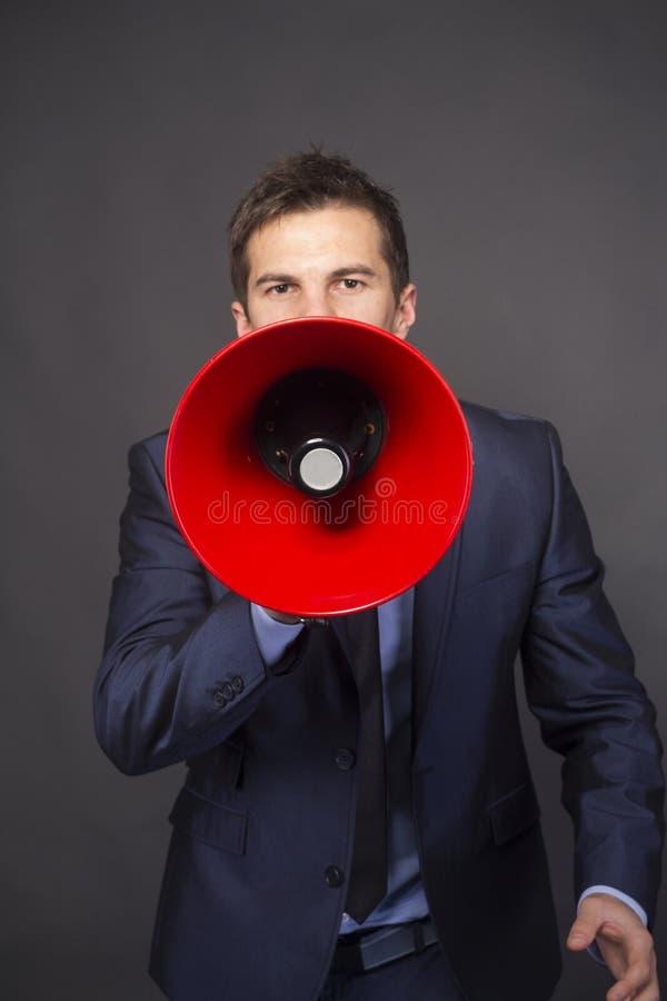 Zakenman die in een megafoon schreeuwen stock foto