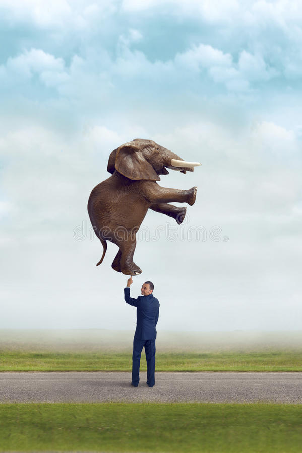 Zakenman die een olifant met één vinger houden stock afbeelding