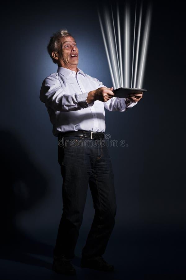 Zakenman die een tablet houden die licht uitstralen stock foto's