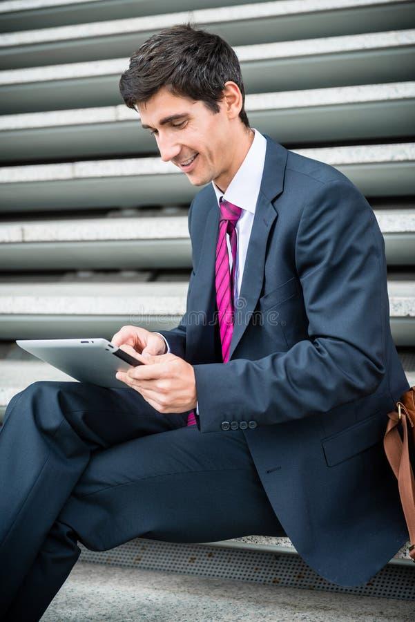 Zakenman die een tablet voor mededeling of gegevensopslag uit gebruiken stock afbeeldingen