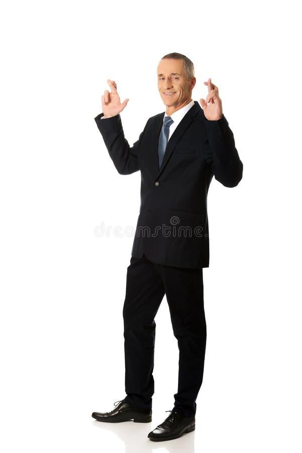 Zakenman die een wens met gekruiste vingers maken stock afbeelding