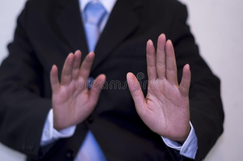 Zakenman die een zwart kostuum dragen, die beide handen, Achtergrondstadslandschap, Anti-corruptieconcept opheffen stock fotografie