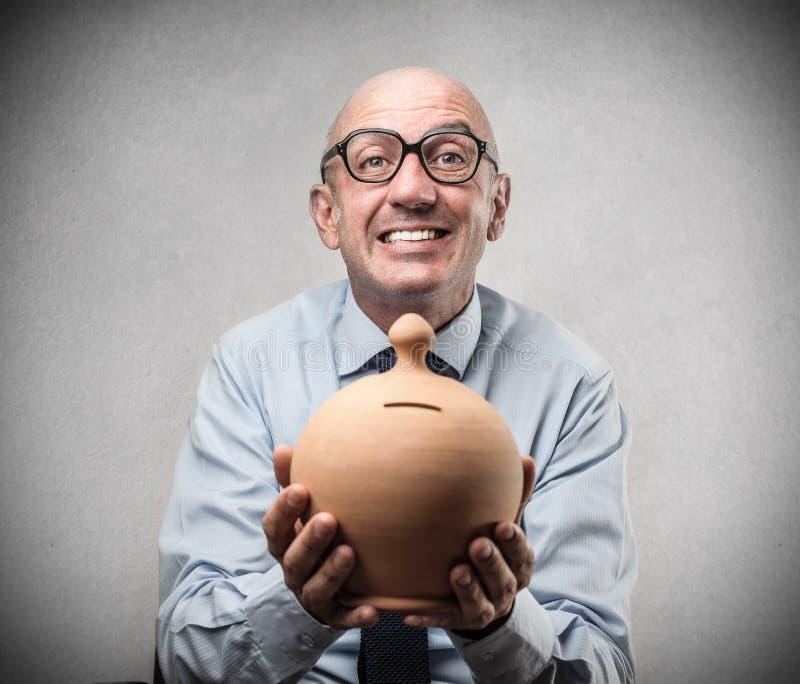 Zakenman die en een spaarvarken glimlachen houden royalty-vrije stock fotografie