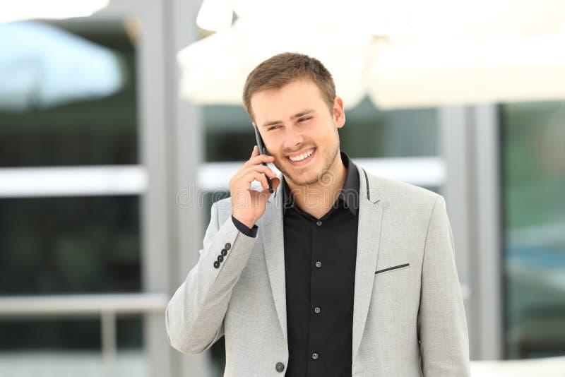 Zakenman die en op telefoon lopen spreken stock afbeelding