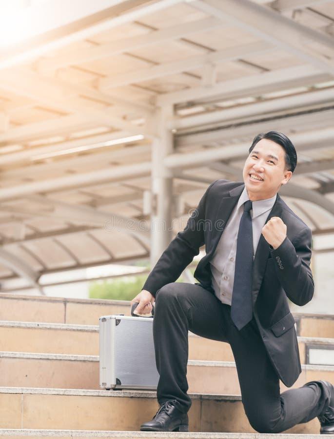 Zakenman die en zijn vuist in de lucht, het bedrijfssucces, de voltooiing, en winstconcepten glimlachen opheffen stock fotografie