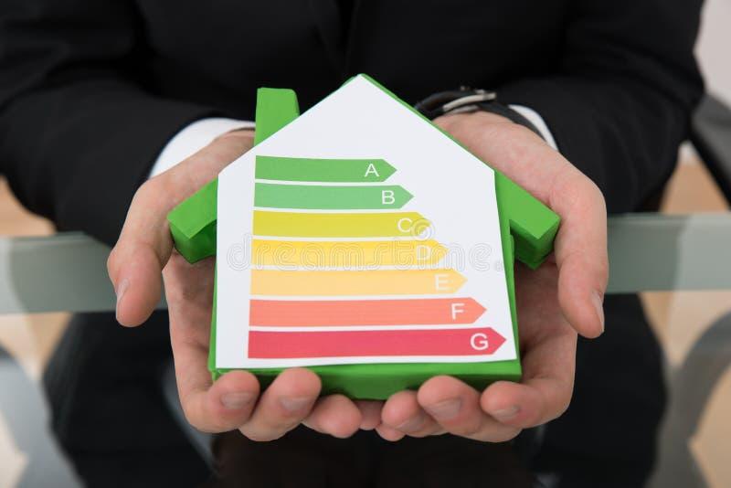 Zakenman die energie efficiënte grafiek op huismodel tonen stock fotografie