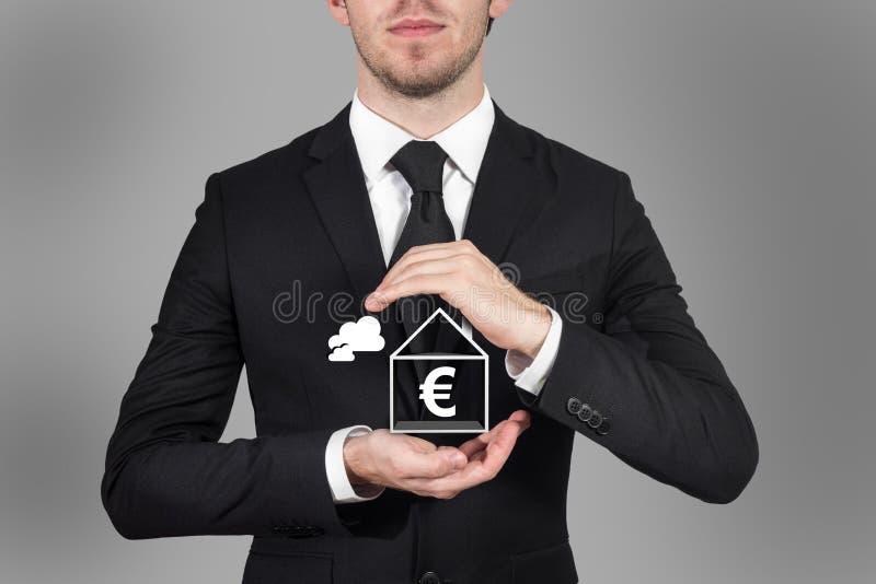 Zakenman die euro symbool in huis met zijn handen beschermen royalty-vrije stock foto