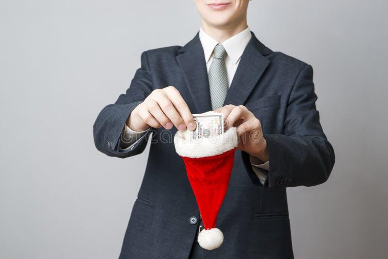 Zakenman die geld in een Kerstmanhoed zetten stock foto's