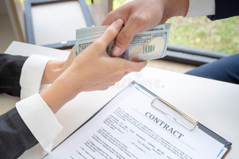 Zakenman die geld geven terwijl het maken van overeenkomst stock foto