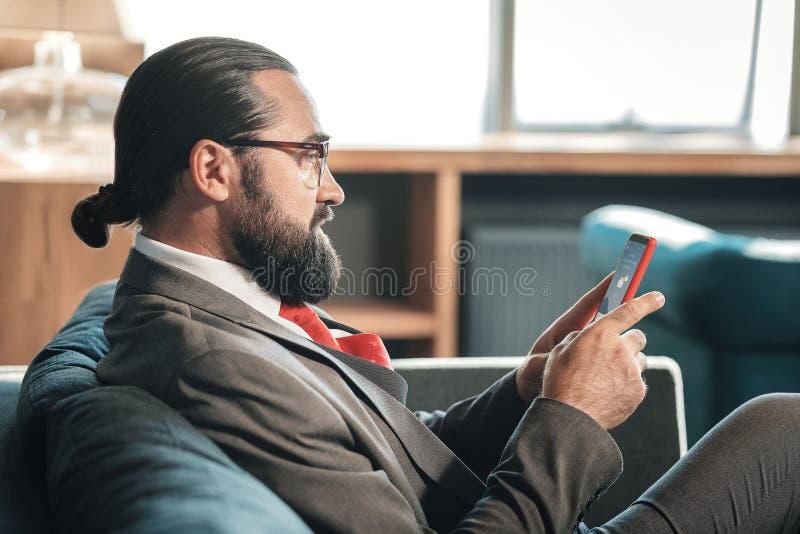 Zakenman die glazen dragen die weervoorspelling controleren op zijn telefoon royalty-vrije stock afbeelding